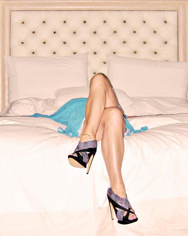 legs crossed on bed-tufted headboard-kirkwood shoes